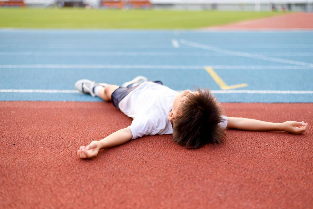 Kid laying down on track, tired.