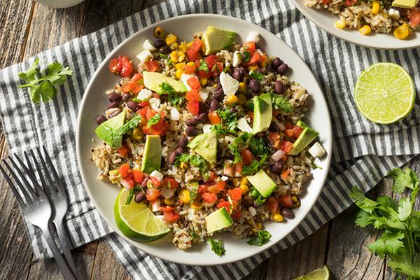A burrito bowl with rice, beans, and vegetables.