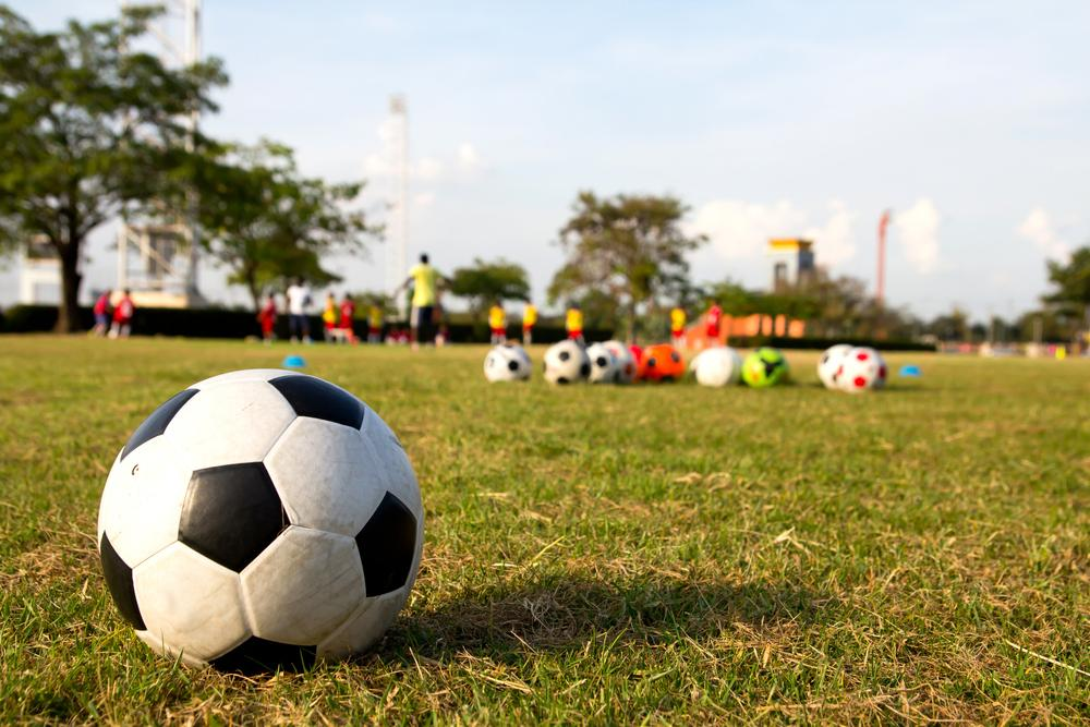 Close up of soccer ball with young athletes in background practicing.