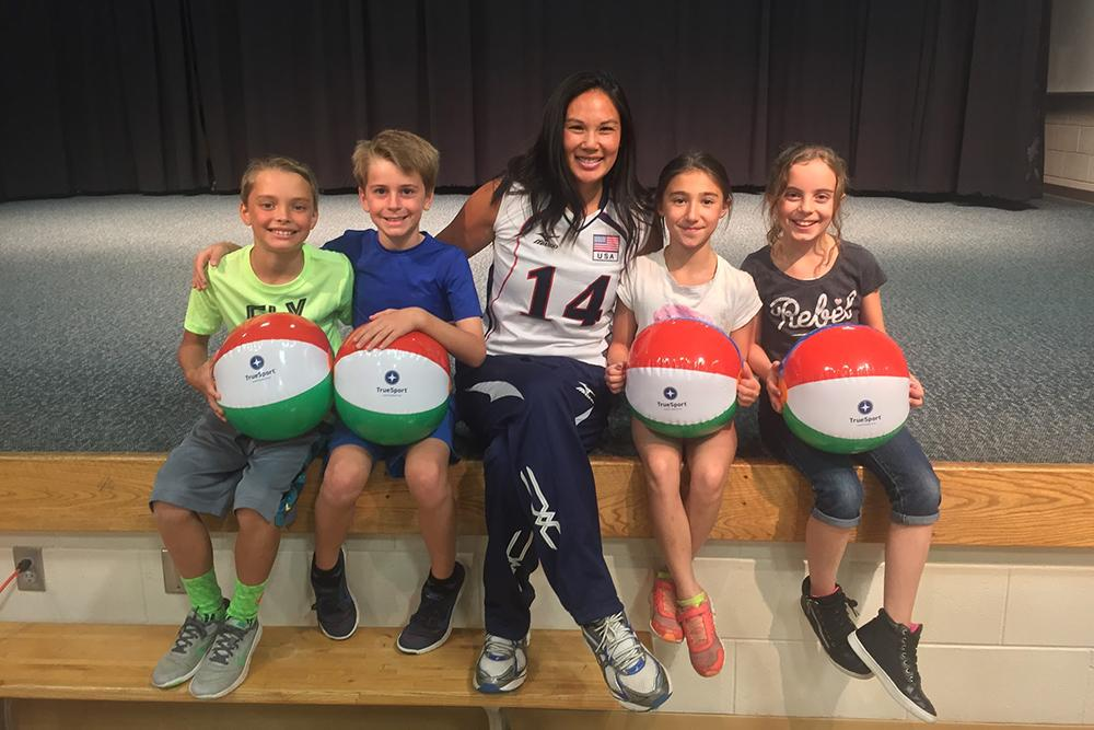 Candace Vering sitting with kids holding TrueSport branded beach balls.