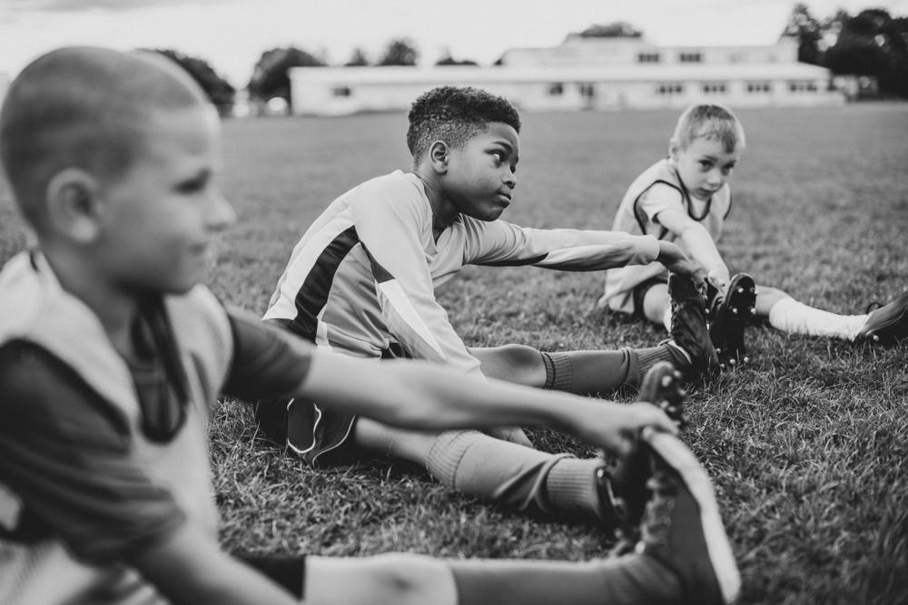 Young diverse boys stretching before sports practice in black and white image.
