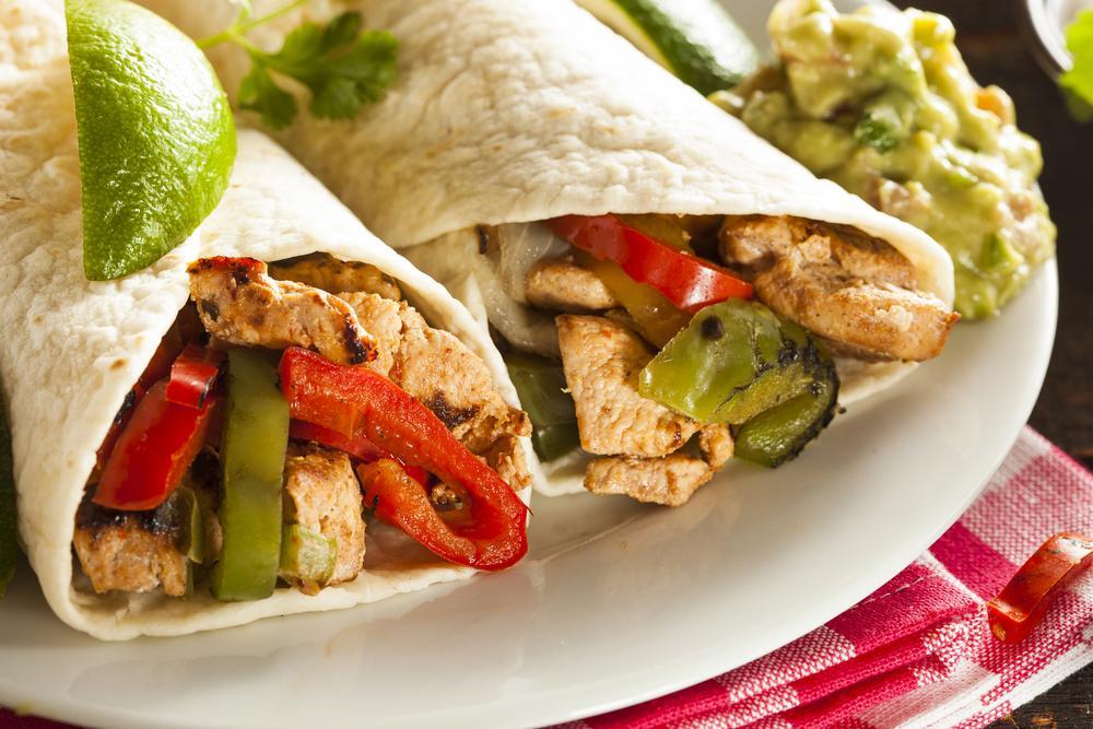 Close up of chicken fajitas in tortillas with a side of guacamole.