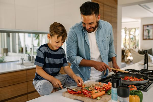 Father and son cooking in the kitchen.