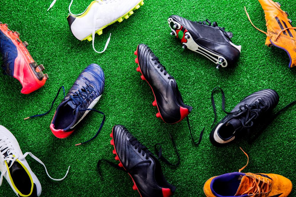 A variety of sport shoes on grass.
