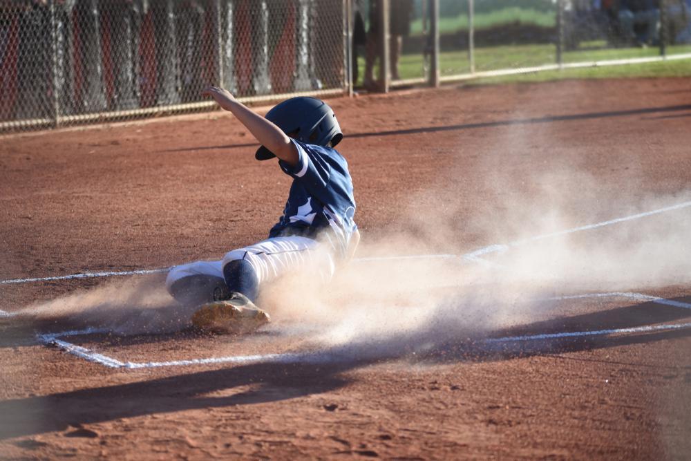 Young boy sliding into home base.