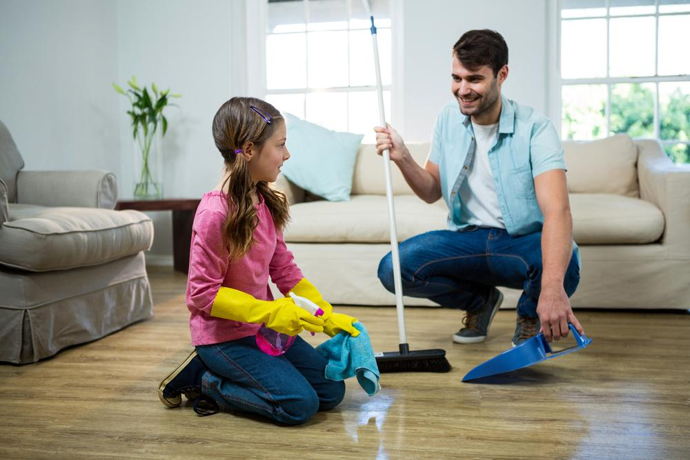 Father and daughter cleaning in house.
