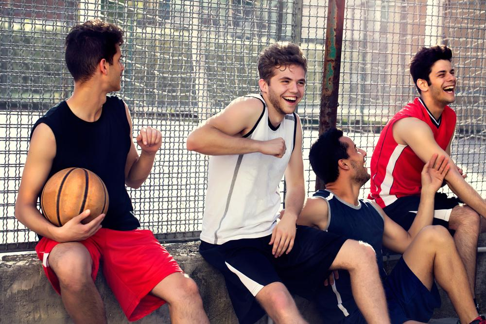 Small group of young men laughing next to basketball court.