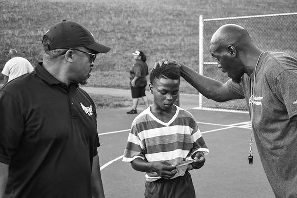 Male coach talking to young soccer athlete in black and white.