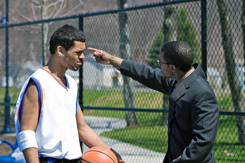 Coach pointing upset at a basketball player outdoors on the court.