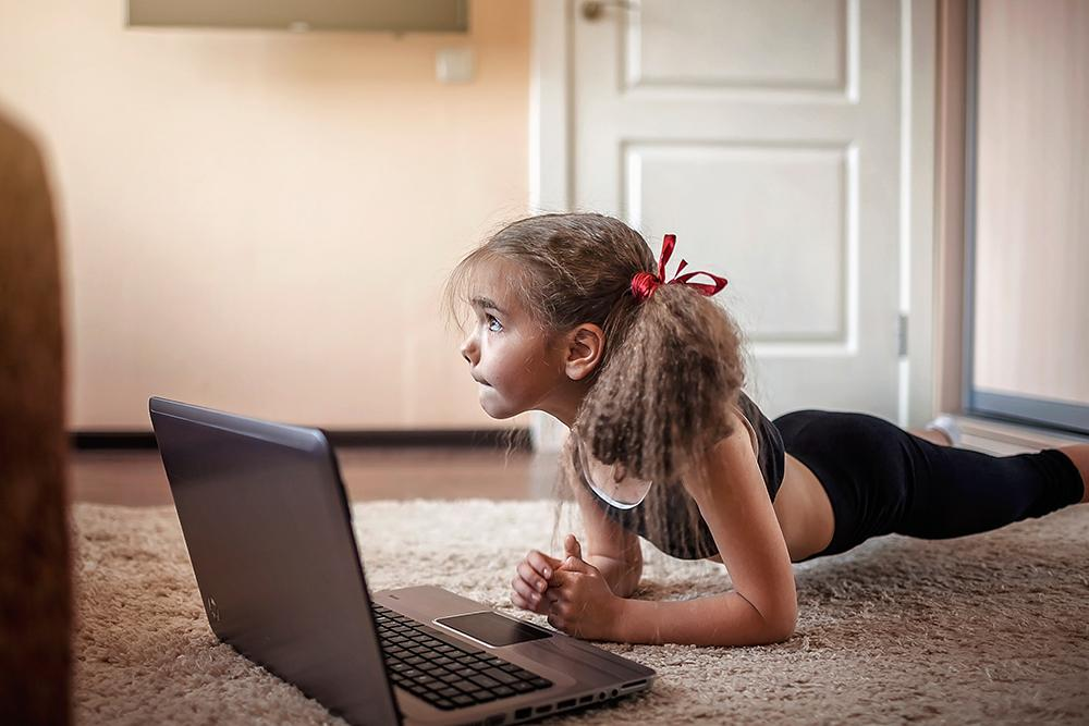 Young girl in workout clothes on laptop on ground indoors.
