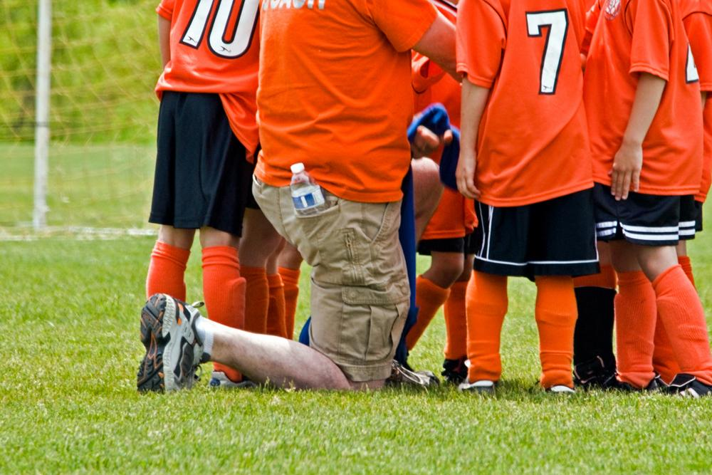 Coach kneeling with young soccer team.