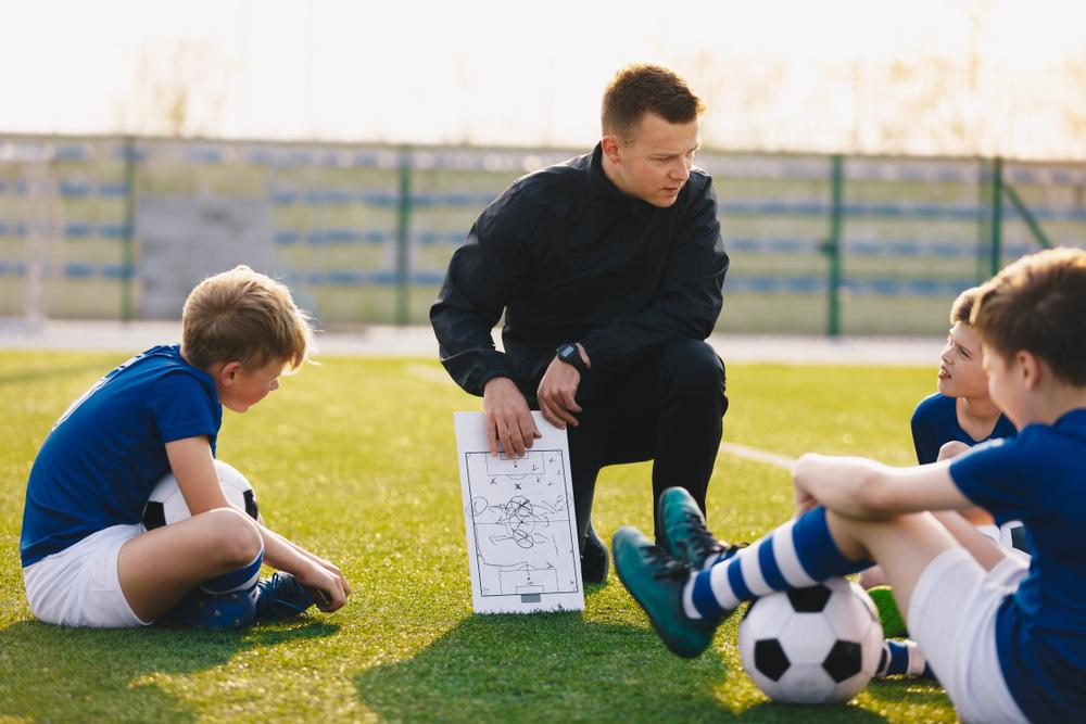 Soccer coach sharing a play with his team.