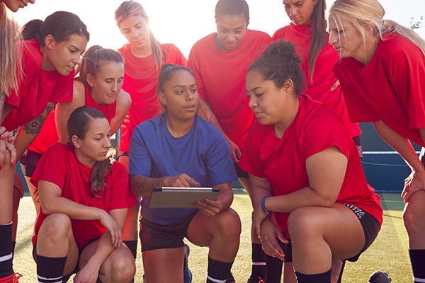 Coach talking to teen girl soccer team.