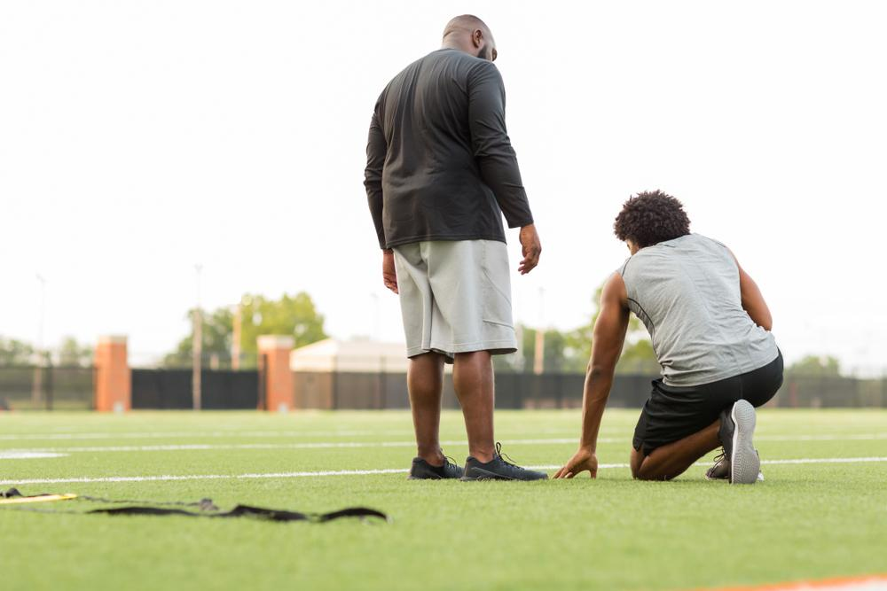 Black male coach talking to young teen male athlete.