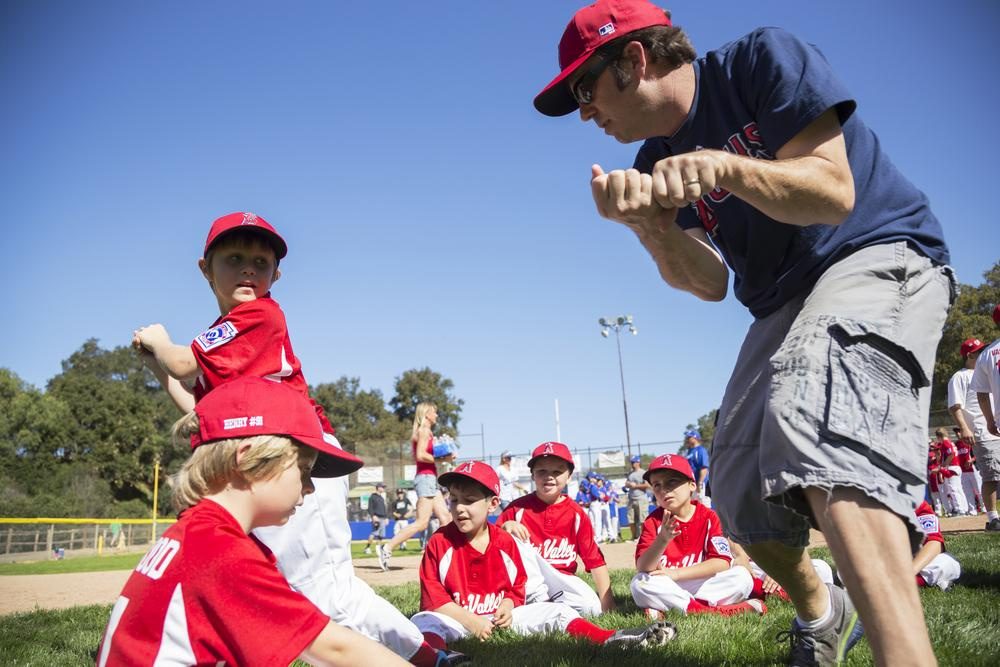 Male baseball coach working with young team.