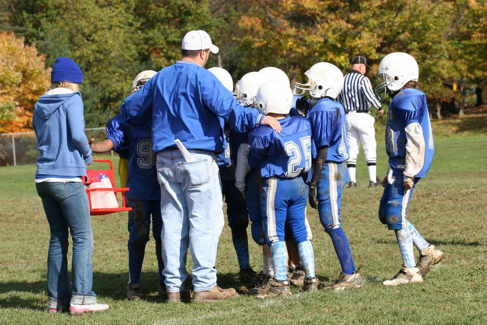 Coach in a huddle with young football players.
