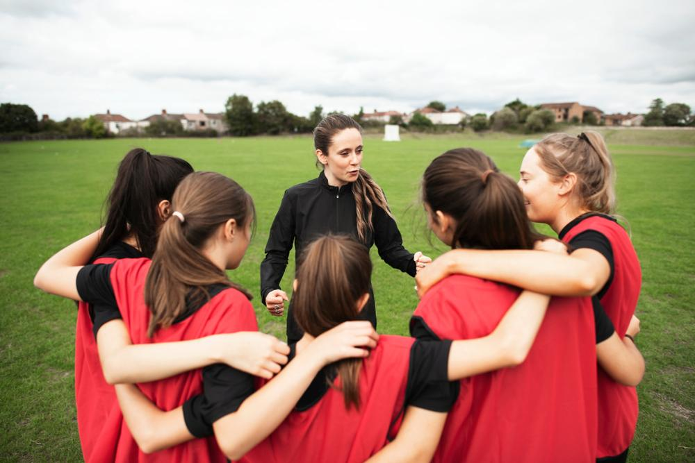 Female coach talking to young female soccer team.