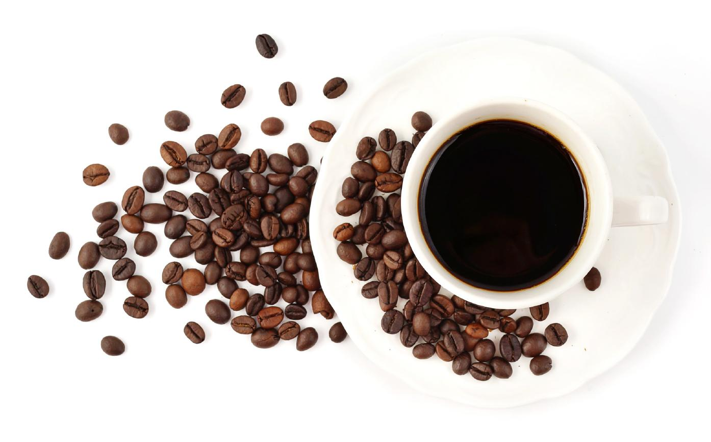 Cup of coffee next to coffee beans on white background.