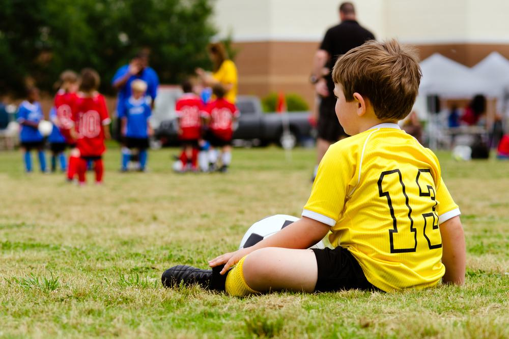Young child sitting on sidelines watching teammates play soccer.