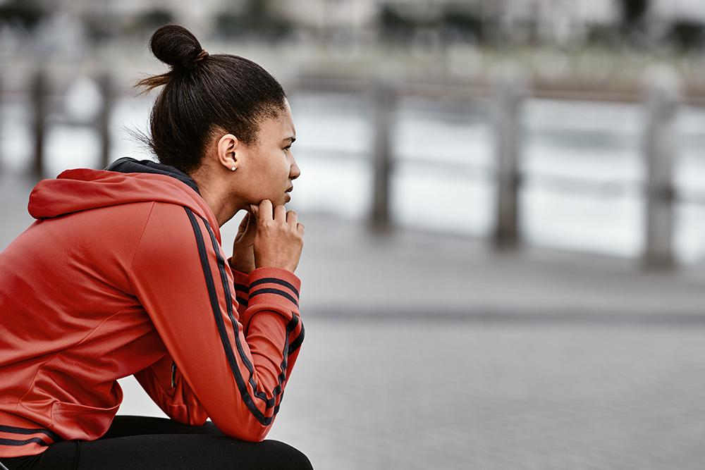 Young black woman wearing jogging clothes sitting and looking contemplative.