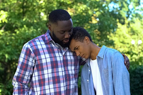 Father comforting teen son.