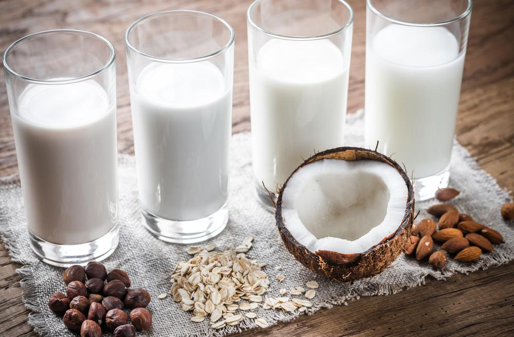 Glasses of milk next to the source, including coconut, almond, and oat.