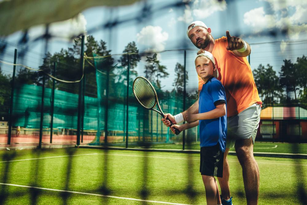 Coach helping young athlete train for tennis.