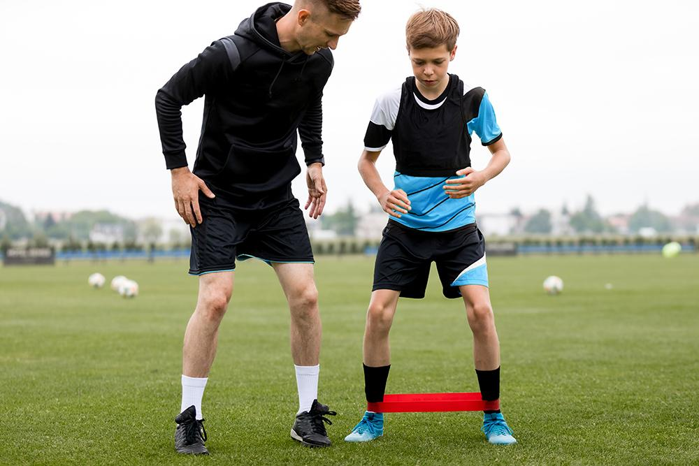 Male coach helping young male soccer athlete.