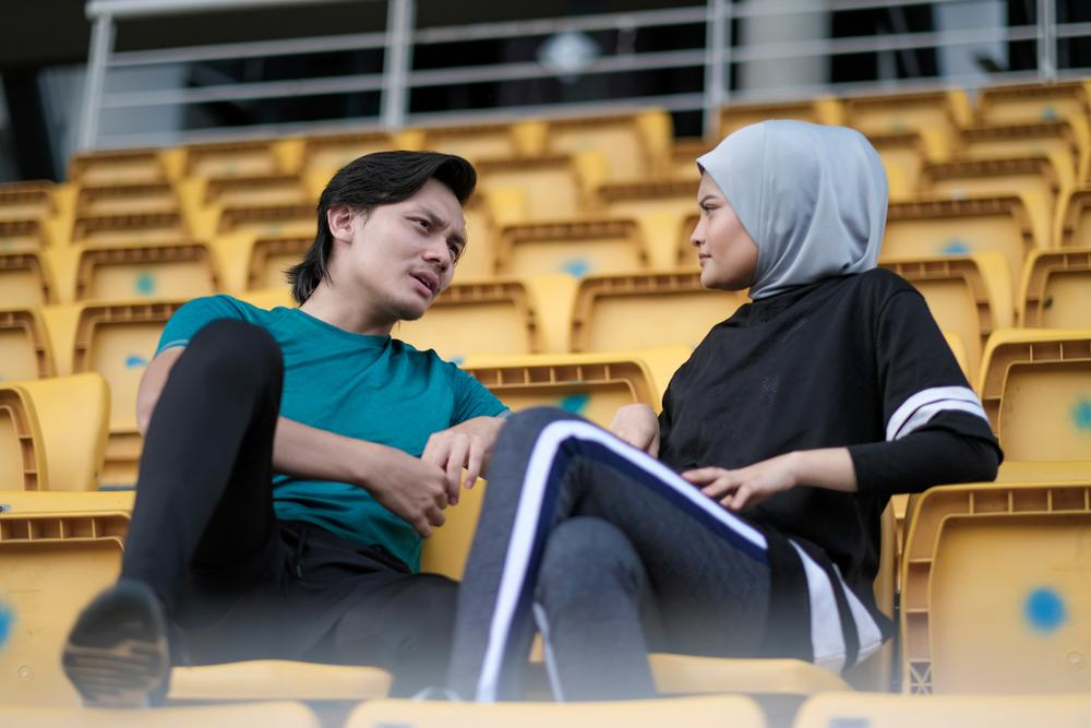 Young man talking to young woman in head scarf in a sports stadium.