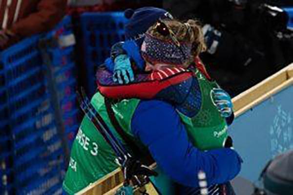 Winter athlete hugging coach.