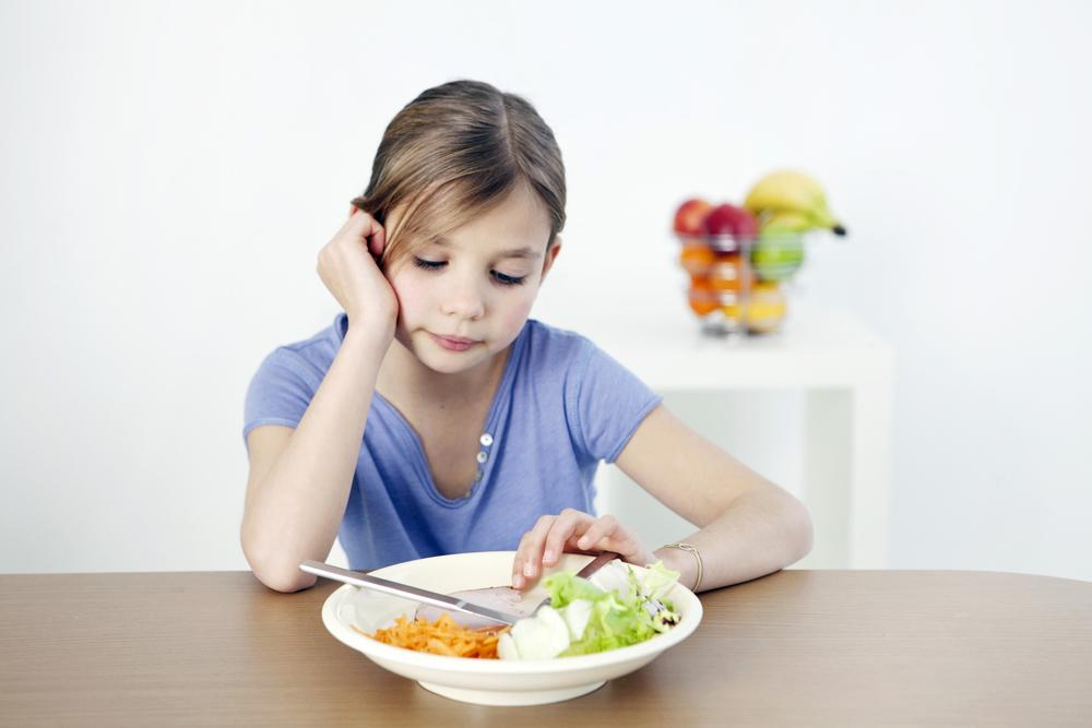 Young girl looking sadly at plate of food.