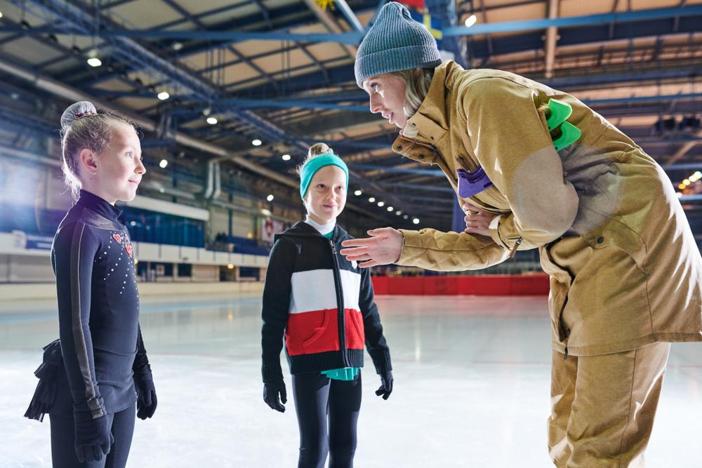 Figure skating coach talking to young athlete.