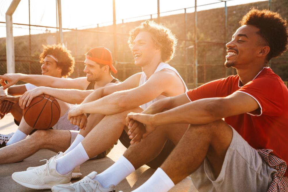Diverse group of young men sitting on basketball court, laughing.