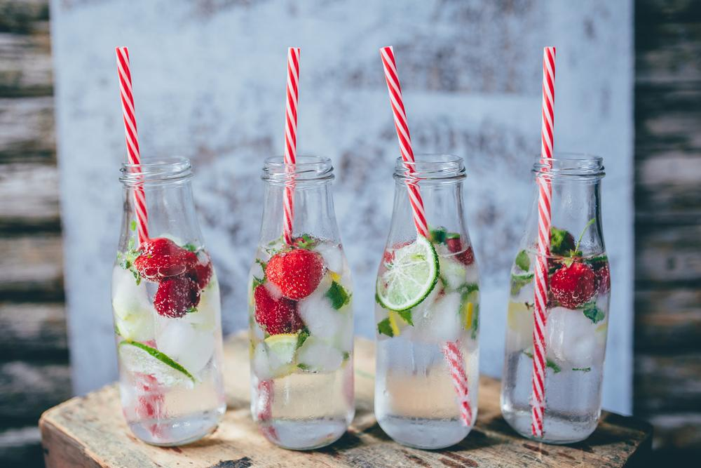 Glasses of water with straws, fruit and ice.
