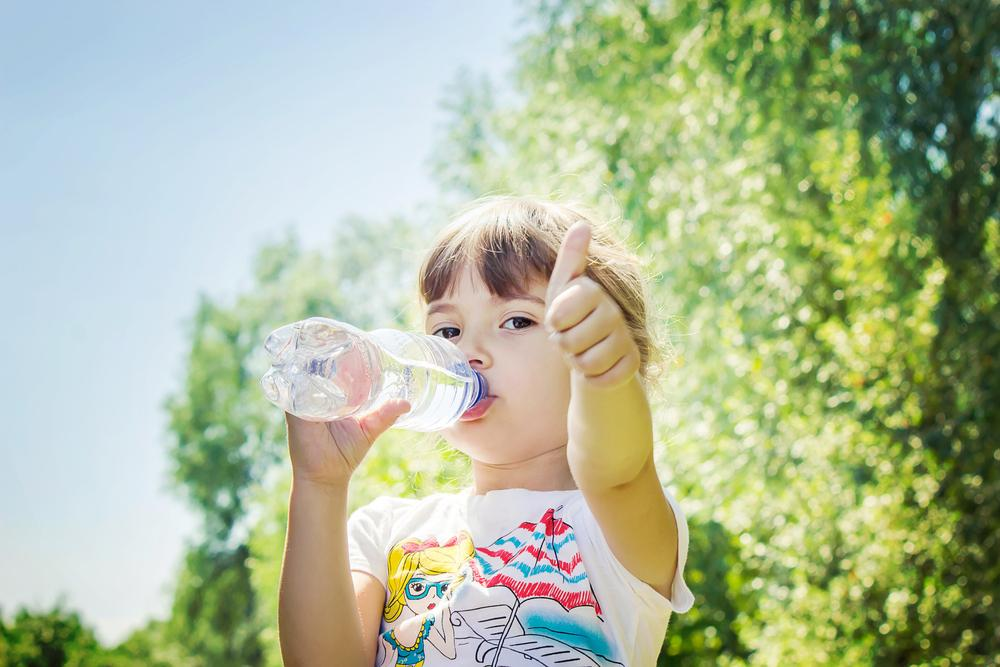 Young girl drinking water from a bottle and giving a thumbs up.