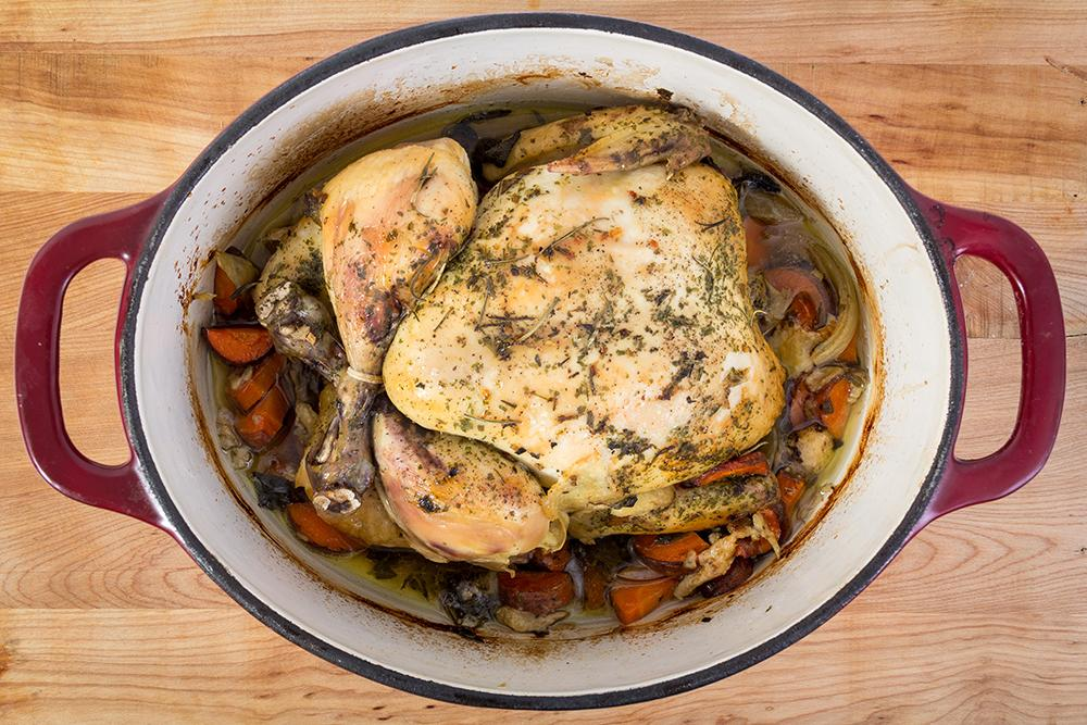 A whole chicken with vegetables fully cooked in a crock pot.
