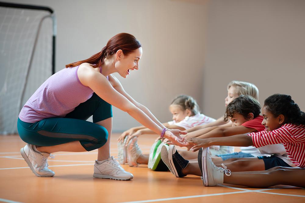 Teacher helping children stretch to their toes in a gym.
