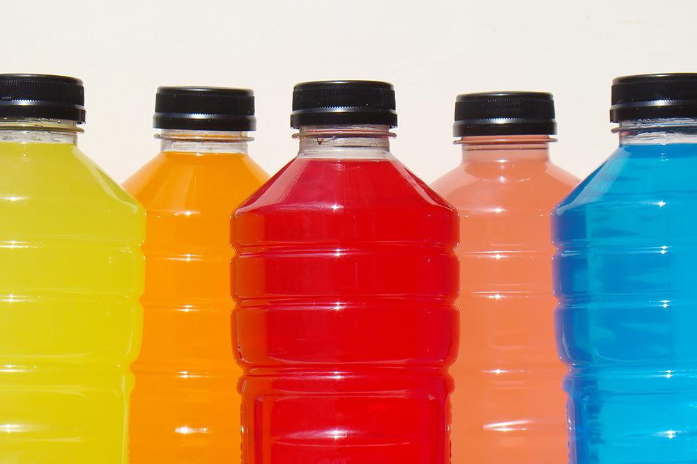 Different colored sports drink on a white background.