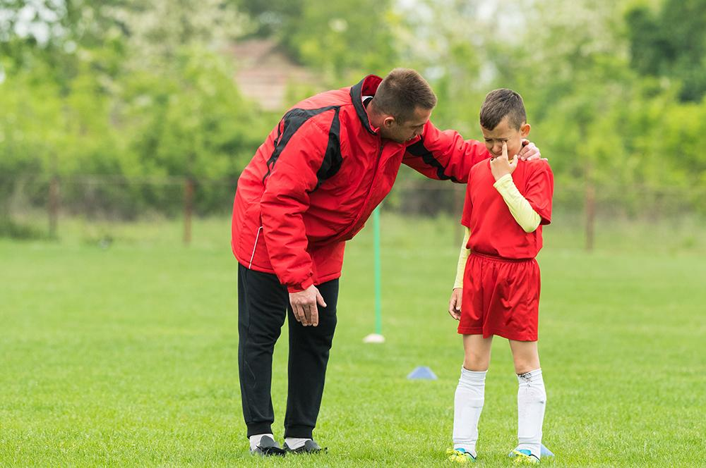 Male coach upsets young male player on soccer field.