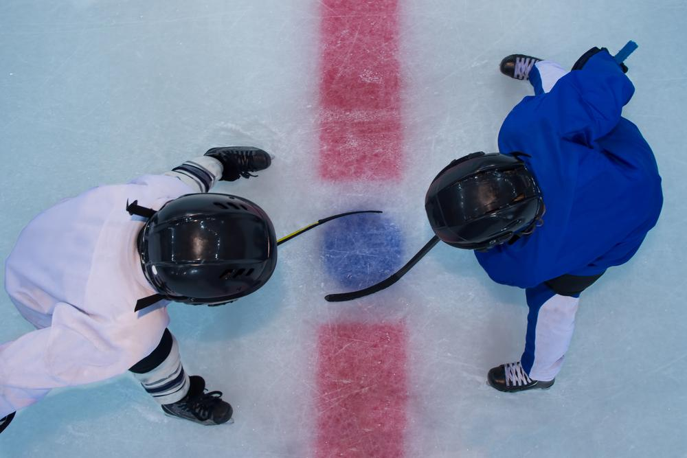 Two young hockey players during a face off.