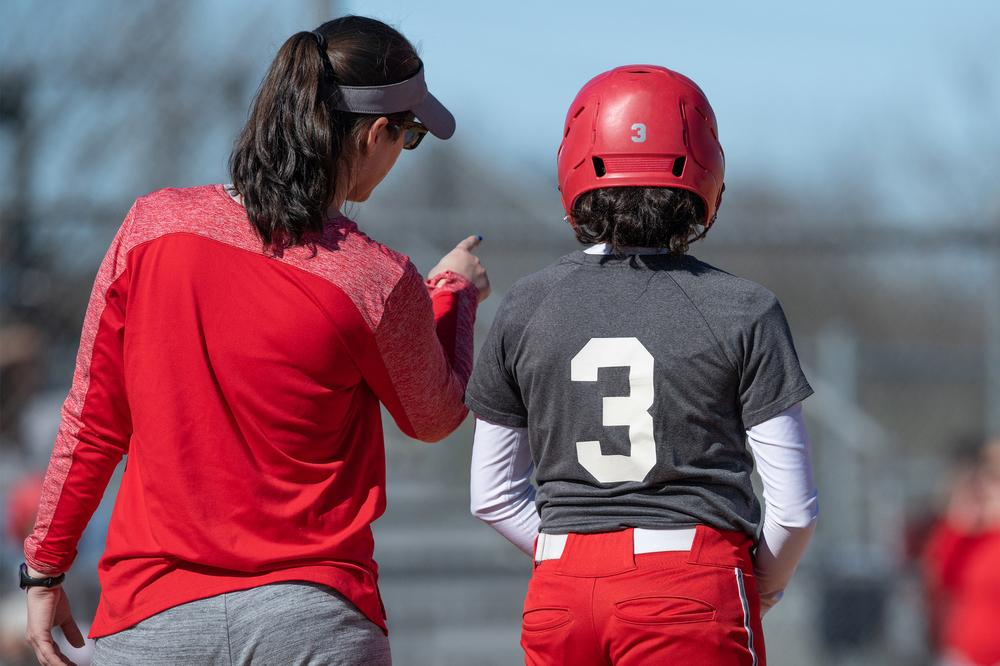 Softball coach talking to young player.