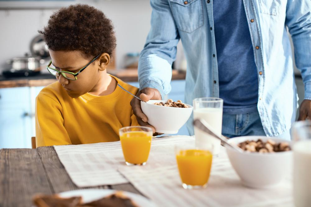 Young boy looking away from bowl of food being delivered by parent.