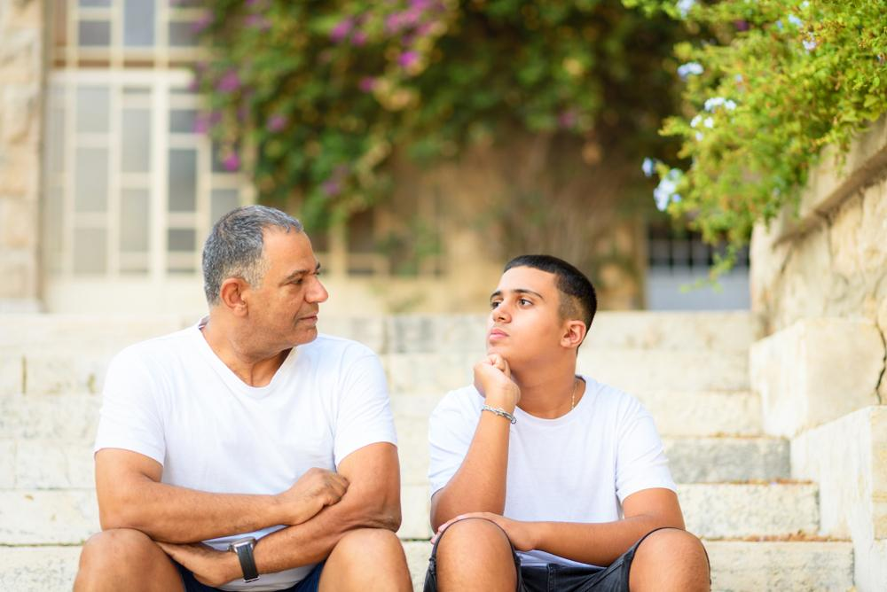 Father talking to teen son on outdoor steps.