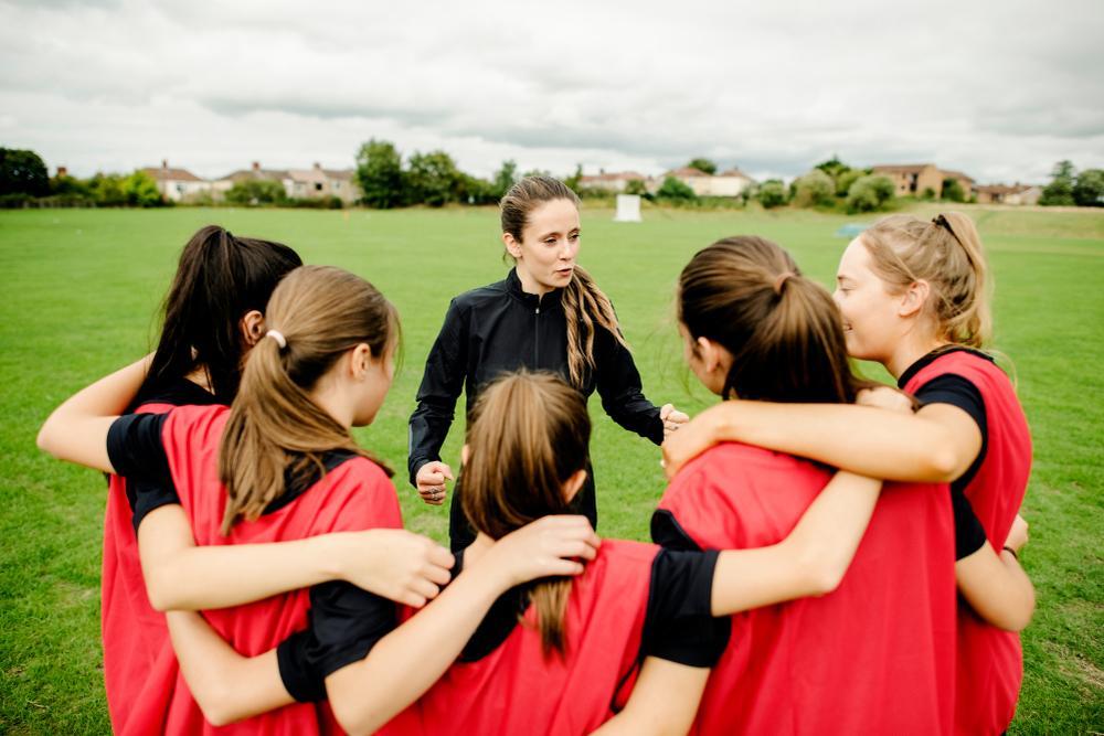 Female coach talking to teen soccer team.