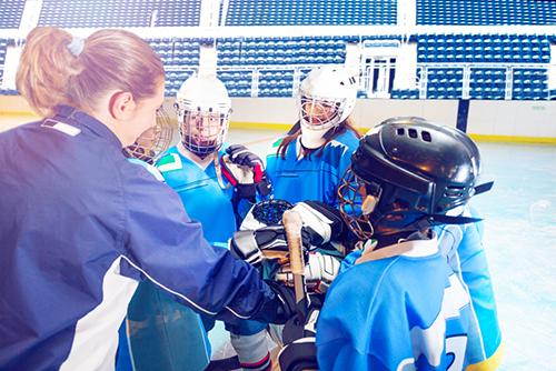 Female hockey coach talking to young team.