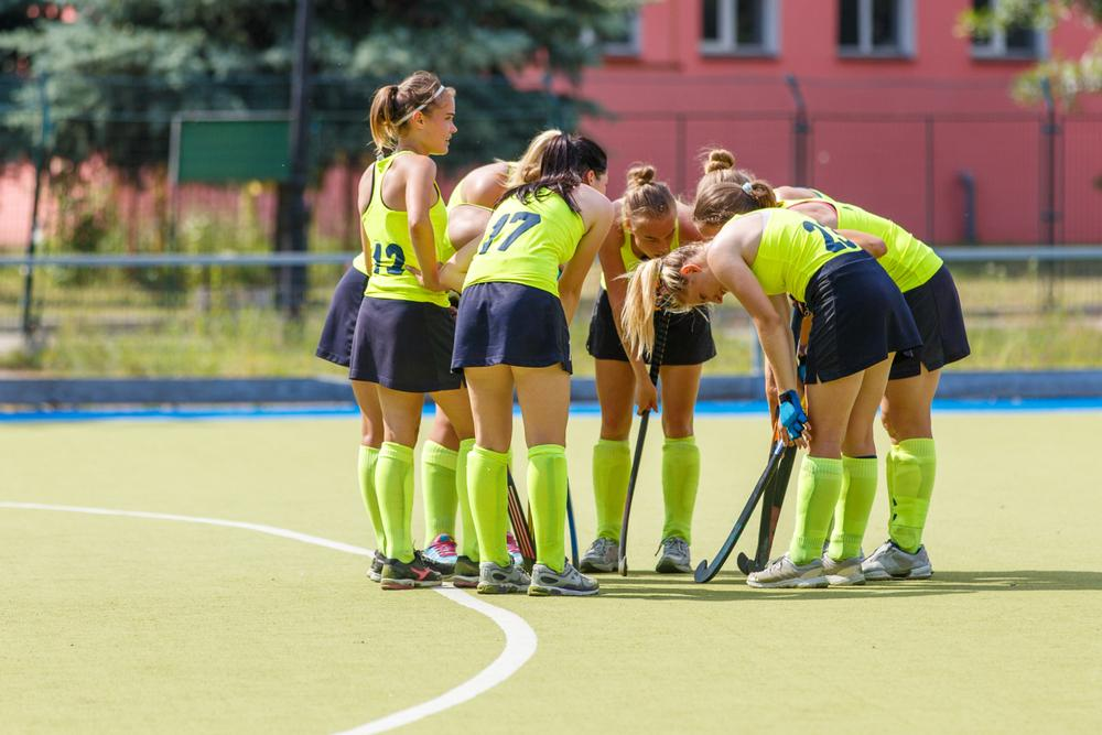 Teen girls huddling during a field hockey game.