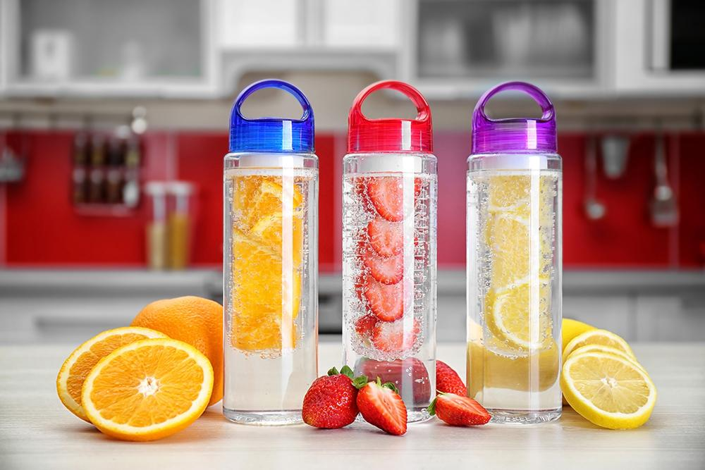 Water bottles with fruit in the water and cut up outside of the bottles.