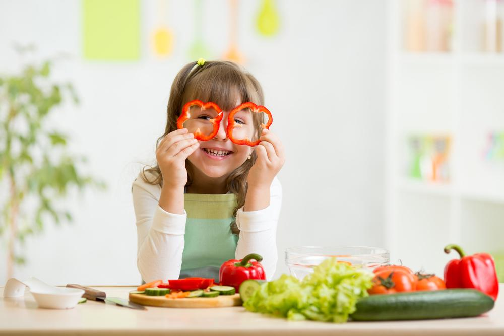 Young girl looking through sliced red peppers.