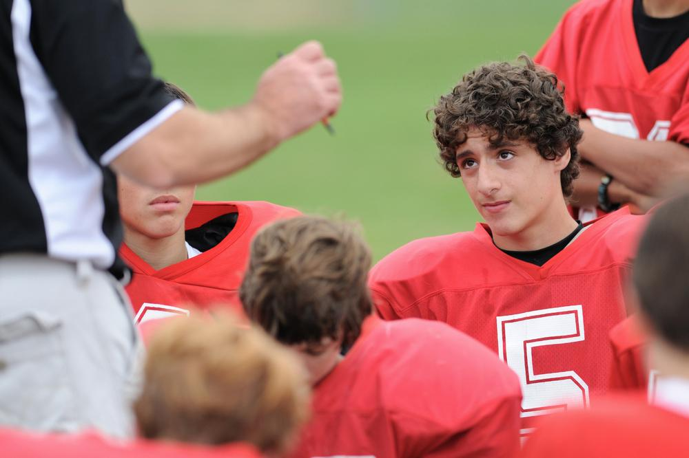 Teen male football player looking at coach.