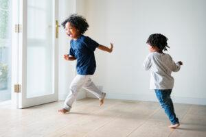 Two young black children running barefoot indoors with smiles.